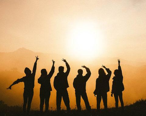 Silhouetten von jungen Menschen am Horizont beim Sonnenuntergang