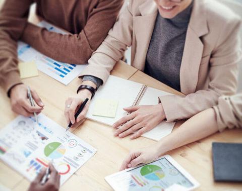 Junge Menschen sitzen an einem Tisch und diskutieren über Arbeit