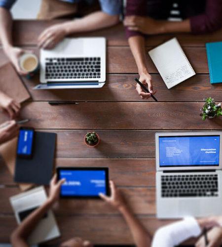 Menschen sitzen an einem Tisch mit Laptops und Kaffee