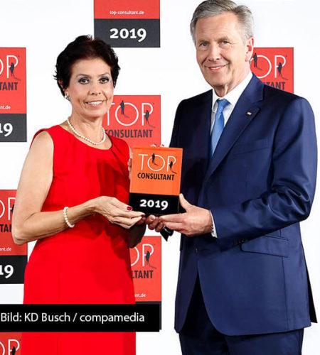 """Christian Wulff überreicht eine """"Top Consultant 2019"""" Trophäe an Consuela Utsch"""